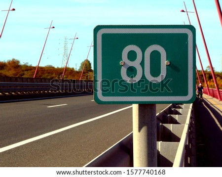 Highway scene in diminishing perspective with 80 km travel distance or milage green and white aluminum sign. road sign and summer landscape on bridge. red painted street lamps. traffic and transport #1577740168