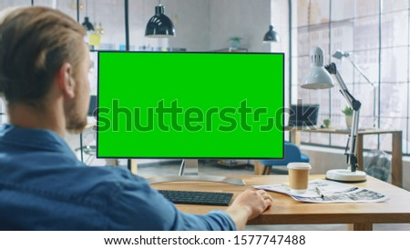 Over the Shoulder Shot: Man Uses Desktop Computer with Green Mock-up Screen while Sitting at His Desk. In the Background Stylish Modern Open Space Creative Business Office
