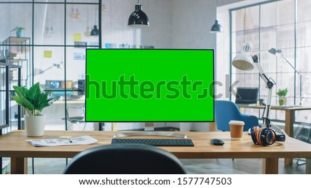 Wide Green Mock-up Screen Desktop Computer Standing on the Desk in the Modern Creative Office. In the Background Bright Creative Loft for Developers and Designers where Professional Working.
