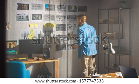 Young Creative Designer Looks at the Storyboard Sketches Covering his Wall, He Chooses Between Concept Drawings, Wondering How to Proceed with this Important Story for His Video Gaming Project