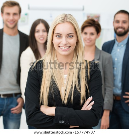 Confident business team with a successful young businesswoman in the foreground smiling at the camera with folded arms #157774937