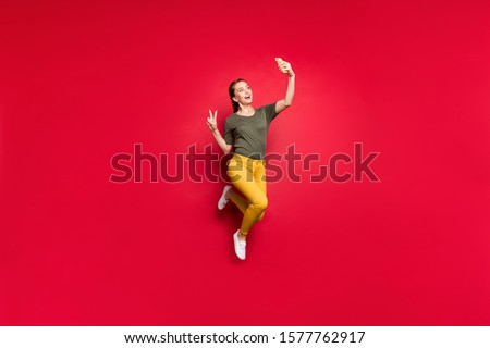 Full body photo of crazy funny lady jumping high making selfies showing v-sign symbol cheerful mood wear casual yellow pants green t-shirt isolated red color background
