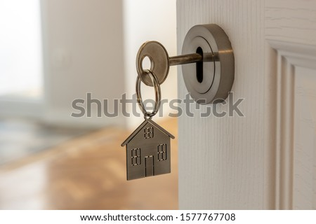 Open door to a new home with key and home shaped keychain. Mortgage, investment, real estate, property and new home concept #1577767708