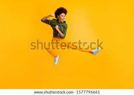 Full length photo of crazy dark skin curly lady jumping high making fighting moves ready to kick leg and fist wear green dotted shirt trousers isolated yellow color background #1577796661