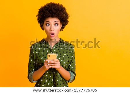 Photo of beautiful shocked dark skin wavy lady open mouth hold telephone read advert unbelievable big shopping prices wear green dotted shirt isolated yellow color background #1577796706