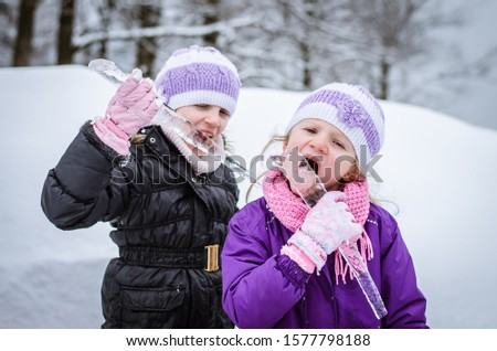 adorable girl having fun with frozen icicles in snowy wonderland Royalty-Free Stock Photo #1577798188