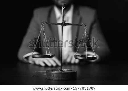 justice and law concept.Male lawyer in the office with brass scale on wooden table,reflected #1577831989