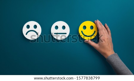 Rating concept. Woman choosing happy smile face emotion on blue background, panorama, copy space #1577838799