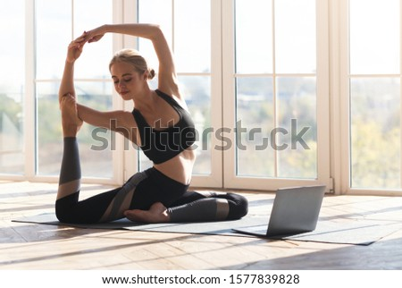 Fitness online. Athletic young woman stretching at home in the morning, using laptop, empty space #1577839828