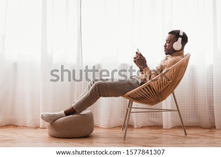 Music Lover. Millennial Afro Guy In Wireless Headphones Using Smartphone Sitting On Modern Chair Next To Window Indoor #1577841307
