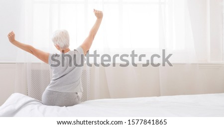 Good morning, world. Well slept senior woman stretching with arms raised on bed, back view, panorama, free space #1577841865