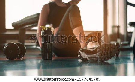 Healthy women are sitting and relaxing after exercising with whey protein after workouts at the indoor gym. #1577845789