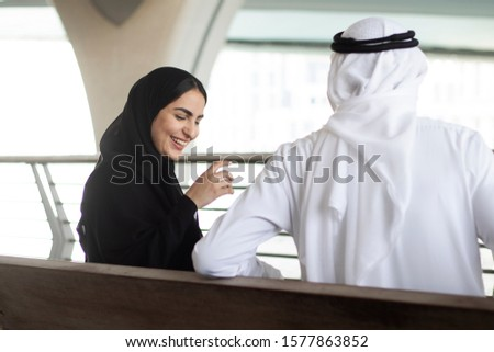 Arabs in relationship talking and laughing together. Happy Arabic couple having fun at an outdoor location. Shot from behind of Middle Eastern woman and man wearing traditional clothes #1577863852
