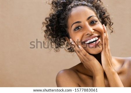 Beautiful young woman smiling after fantastic face treatment. Happy beauty african girl excited after spa treatment isolated on background with copy space. Surpise and astonishment beauty concept. #1577883061
