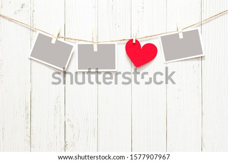 Empty photo frame and red heart shape garland on wood background