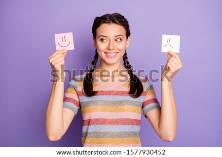 Photo of funny lady holding paper emoticons good and bad mood picking positive emotions wear casual striped t-shirt isolated pastel purple color background
