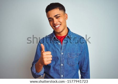 Young brazilian man wearing denim shirt standing over isolated white background doing happy thumbs up gesture with hand. Approving expression looking at the camera with showing success.