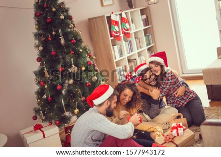 Group of friends sitting next to nicely decorated Christmas tree, having fun while celebrating Christmas at home, exchanging Christmas presents #1577943172