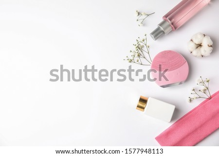 Composition with face cleansing brush on white background, top view. Cosmetic accessory