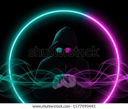 Silhouette of the unknown person in a hood with the mobile phone in a hand in the dark, with colorful vivid neon lights #1577990443