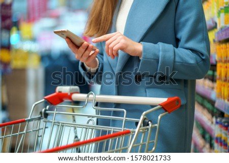 Woman buyer with cart in the store aisle with grocery list on smartphone during shopping food  Royalty-Free Stock Photo #1578021733