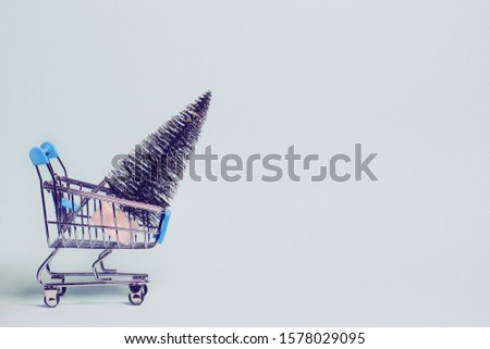 Small decorative trolley decorative fir tree on bright colorful background. Christmas or birthday gift. Sales and shopping concept.  Image is with copy space #1578029095