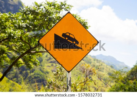 Yellow road sign car down. Steep descent of the road