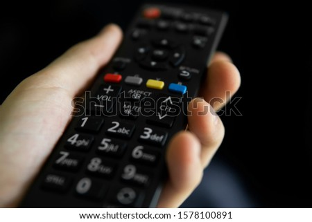 Close up on a man's hand with the remote control want switch on the TV and presses the button on the remote control. Remote control in hand closeup. #1578100891