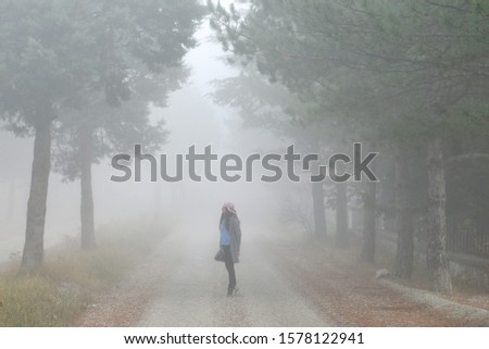 A girl with pink hat walks into foggy forest road #1578122941