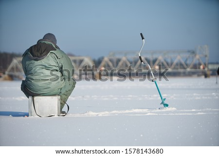 Fisherman enjoying a days fishing on the ice Royalty-Free Stock Photo #1578143680