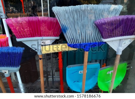 Bucharest, Romania - October 10, 2019: Several colored plastic brooms are displayed in the window of a shop in Bucharest. This image is for editorial use only. #1578186676