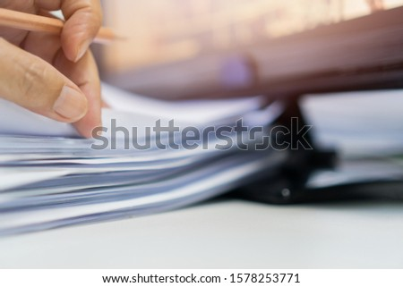 Business man manager holding pencil for checking and signing applicant filling documents reports papers company application form or registering claim on desk office #1578253771