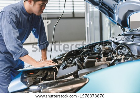 Asian Man mechanic inspection writing note on clipboard insurance notepad with car engine.for transport automobile automotive image. #1578373870