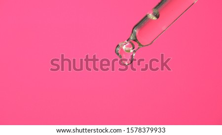 Oil or liquid dropper or pipette in extreme macro close up. Drop of yellow cosmetic lavender oil falling on pink background. Eyedropper squeezing out meds droplets. #1578379933