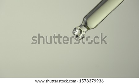 Oil or liquid dropper or pipette in extreme macro close up. Drop of yellow cosmetic lavender oil falling on white background. Eyedropper squeezing out meds droplets. #1578379936