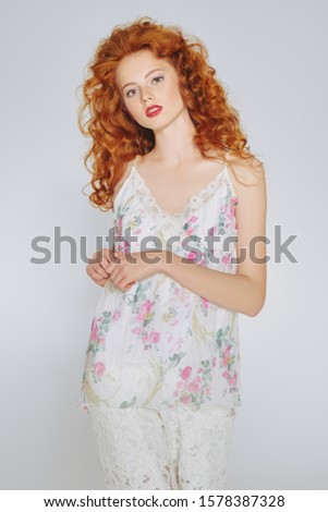 Beautiful fashion model with long curly hair posing at studio. Light summer style. White background. Copy space.  #1578387328