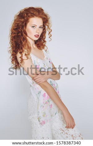 Beautiful fashion model with long curly hair posing at studio. Light summer style. White background. Copy space.  #1578387340