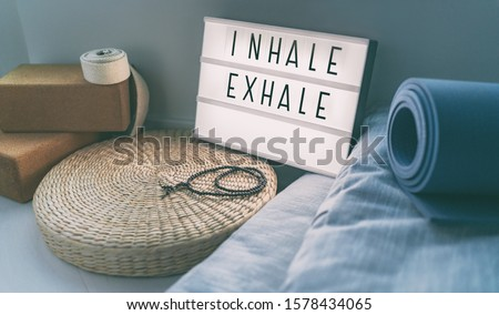 Yoga breathing INHALE EXHALE sign at fitness class on lightbox inspirational message with exercise mat, mala beads, meditation pillow. Accessories for fit home lifestyle. #1578434065