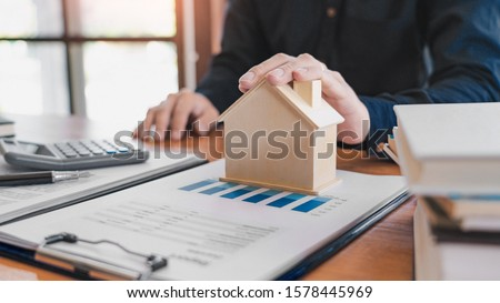 buy or sell real estate concept, Sale representative offer house purchase contract to buy a house or apartment and give home key chain to customer #1578445969