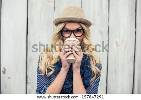 Smiling fashionable blonde drinking coffee outdoors on wooden background #157847291