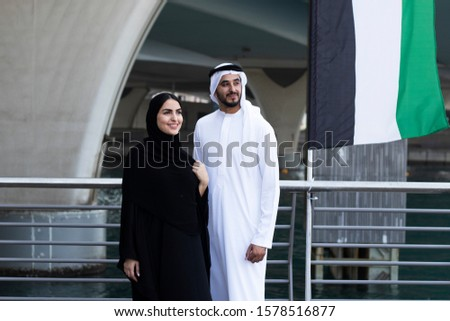 Couple in Abaya and Kanudra looking far with happy face. Smiling Arabs wearing cultural UAE clothing in the Middle East, Gulf countries. Arabic husband and wife concept #1578516877