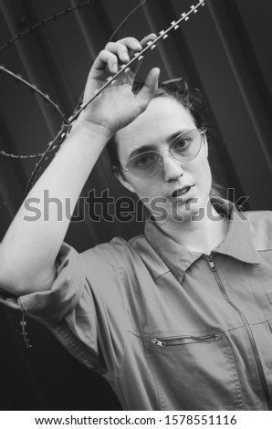 Black and white shot of Young woman in red overalls and red sunglasses posing with barbed wire. Women concept #1578551116
