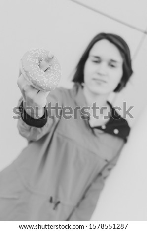 Black and white shot of Beautiful woman showing fuck with donut Diet diet concept. Junk food, weight loss. #1578551287