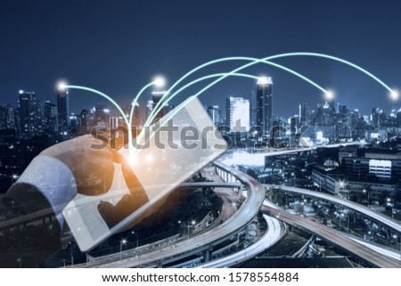 double exposure, close up hand of businessman using tablet with night cityscape skyscrapers with connected line network, business partner connect concept. #1578554884