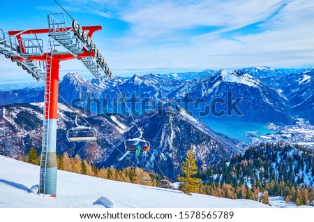 The chairlifts of Feuerkogel Mount offer the breathtaking journeys over the steep snowy slopes and Traunsee lake valley, Ebensee, Salzkammergut, Austria #1578565789