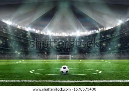 soccer stadium in the evening - ball in midfield Royalty-Free Stock Photo #1578573400