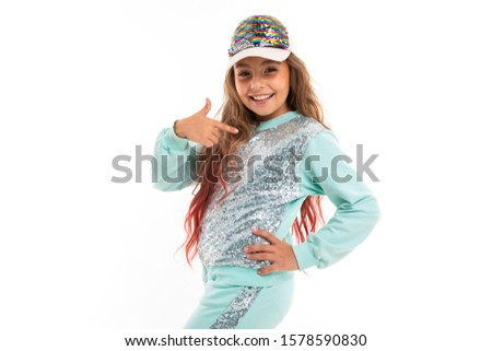 Little pretty caucasian girl in a tracksuit smiles and shows herself, picture isolated on white background