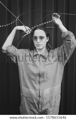 Black and white shot of Young woman in red overalls and red sunglasses posing with barbed wire. Women concept #1578615646