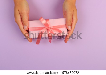 gift in female hands on a colored background top view. #1578652072