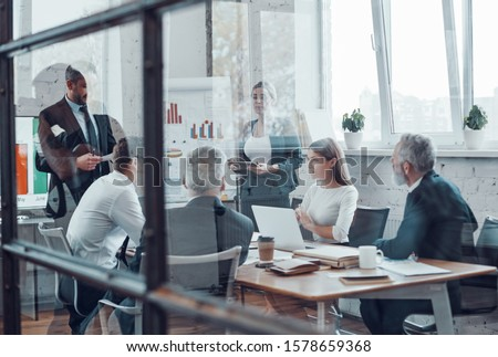 Professional business expert presenting analytical report while working together with colleagues in the modern office #1578659368